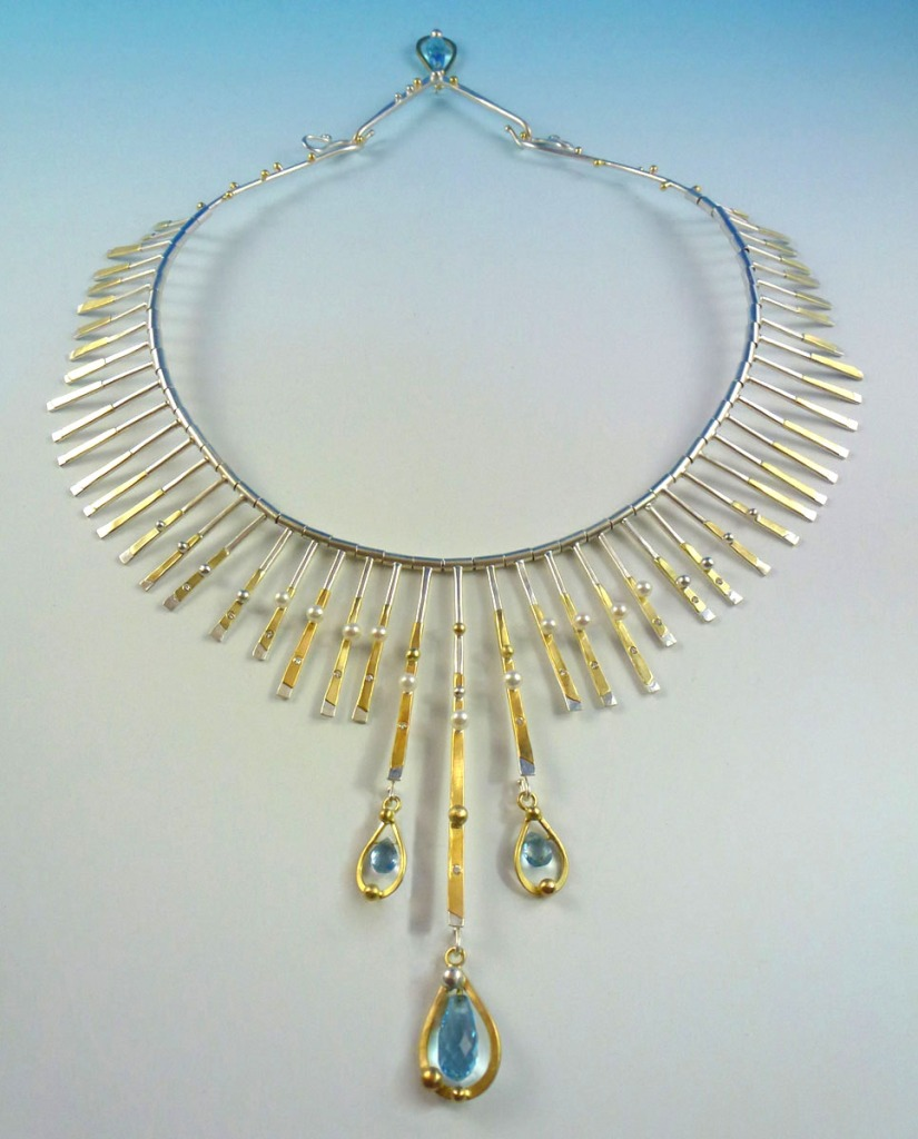 Sunrise Necklace: Made of sterling silver, 18kt gold, 24 kt gold and blue topaz briolettes.