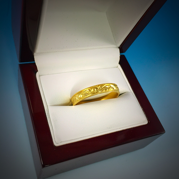 This 18kt gold ring was a custom piece made as a wedding band for a client. It is engraved with a floral pattern.