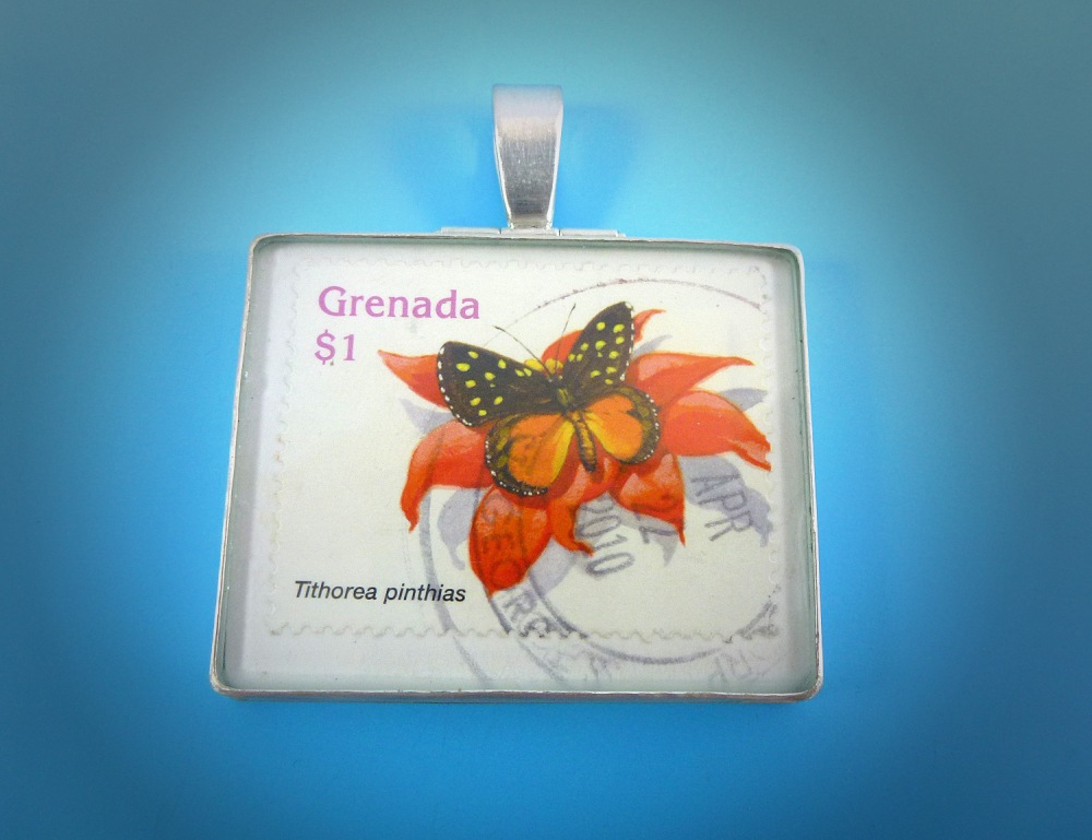 This silver pendant was made from a piece of a postcard that a client received from her son. I made a custom silver frame pendant to encapsulate the postcard. The postcard is set between two panes of glass. The bail on the top is hinged to allow for movement.