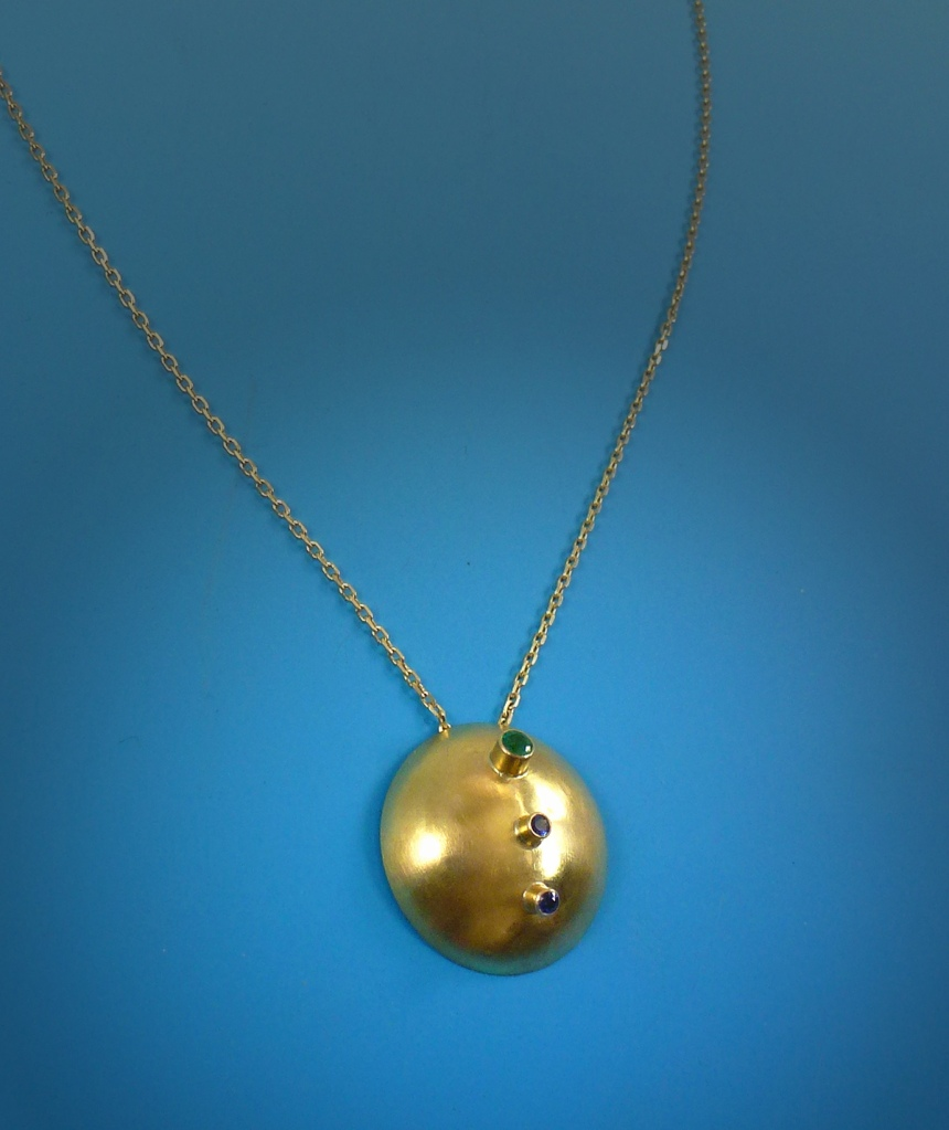 Detail image of gold disk necklace.