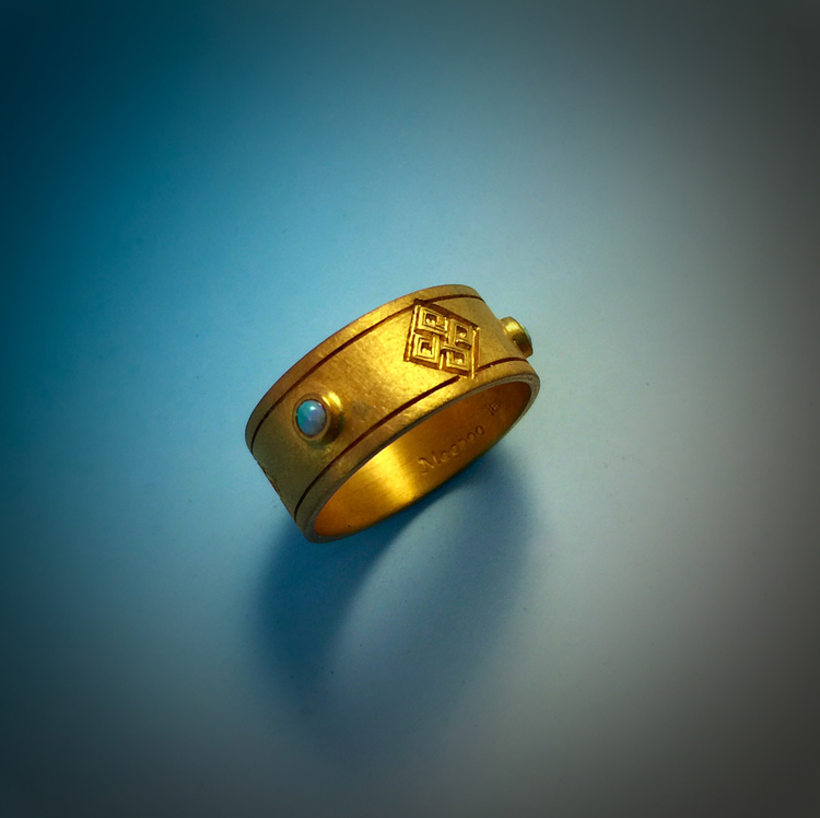 This is a custom 18kt gold wedding band. The ring is engraved with Lewis Chessman knotwork and set with small opals.