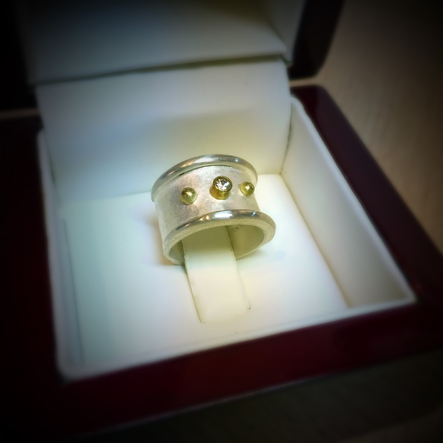 I made this wide band as a wedding band for a client. The ring is made of sterling silver, 14kt gold and white sapphire.