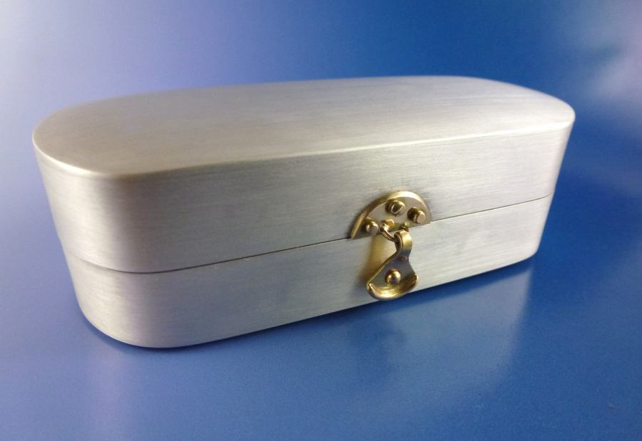 I fabricated this custom silver box for a client to hold their reading glasses. I made the clasp in the front in 14kt gold.