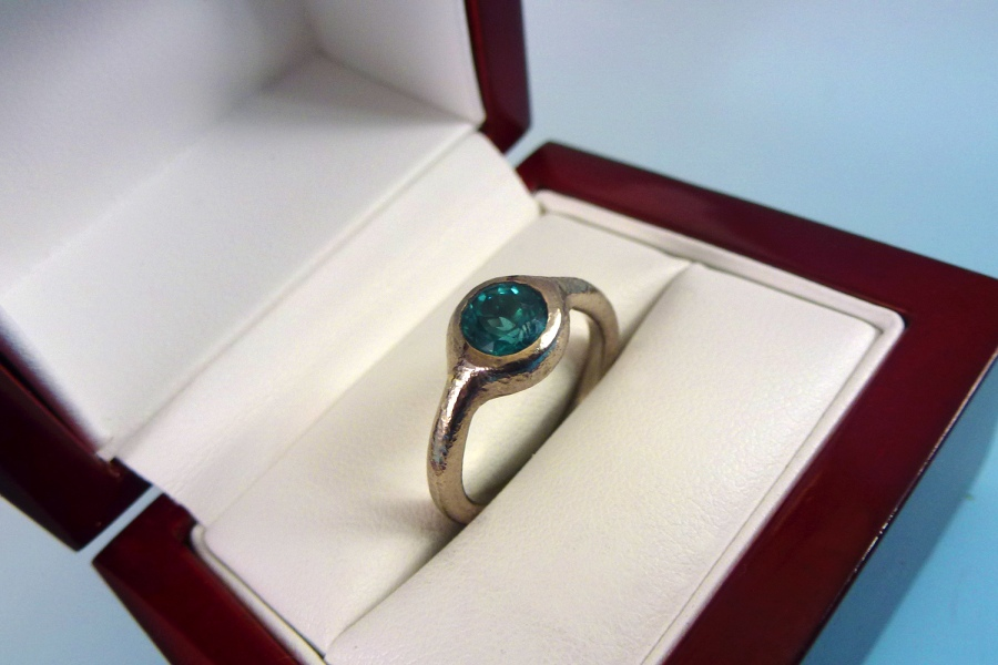 This hammered 14kt white palladium gold ring was made as an engagement ring for a client. The ring is set with a round brilliant blue tourmaline.