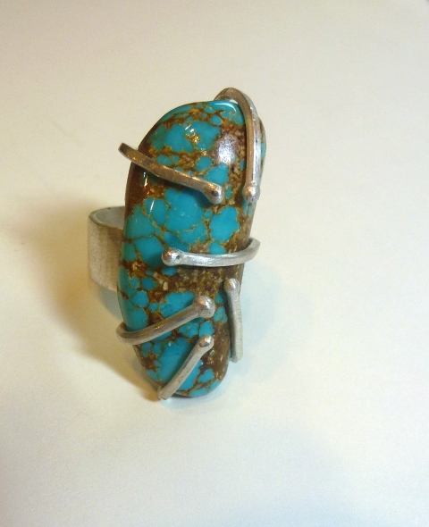 This is an example of modified prong setting made by student, Brighid Lambert. She fabricated this ring out of sterling silver and turquoise.