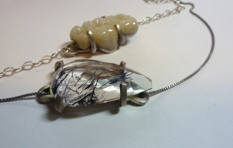 These two pendants utilize modified prong settings. These pendants are made of sterling silver, rutilated quartz and porcerlain teeth by student, Ericka Murillo.