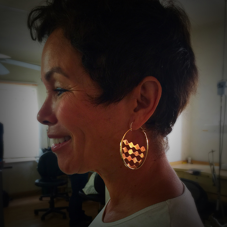 Student, Robyn Hood, modeling her finished pair of hoop earrings.