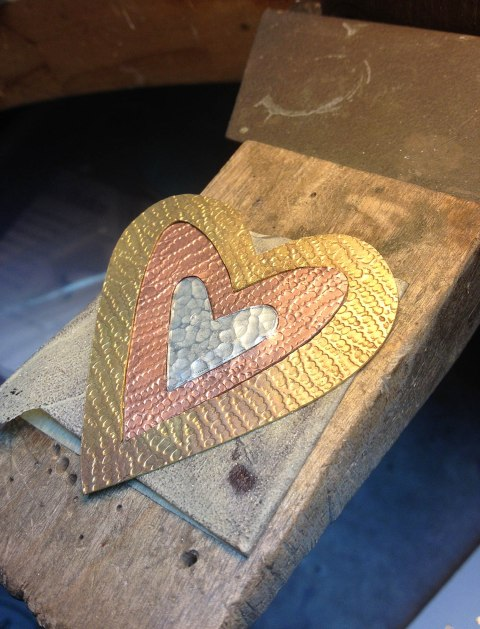 This is a heart pendant in progress made by Lindy Hartig. Her piece is made of sterling silver, brass and copper. She textured each of the various metals for a more enhanced look.