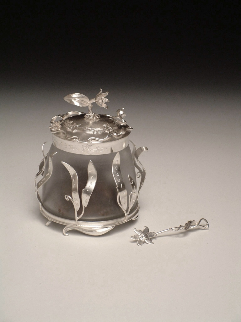 "Creme de la Terre: This piece was a part of my MFA thesis exhibition, ""Instruments of Vanity"". I fabricated this jar and spatula out of sterling silver, glass, lotion, and fishing tackle."