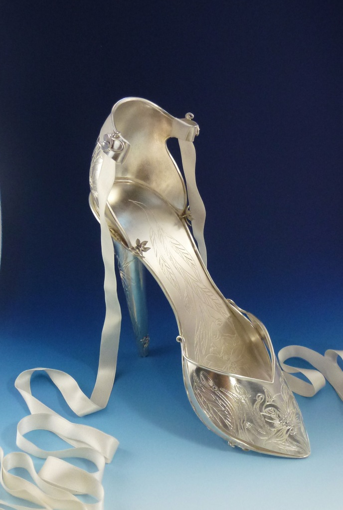 Oleander Stiletto: This is a full size stiletto shoe fabricated in sterling with a silk ribbon tie. The entire shoe is etched with an oleander flower pattern. Though beautiful, the plant is highly toxic and therefore dangerous.